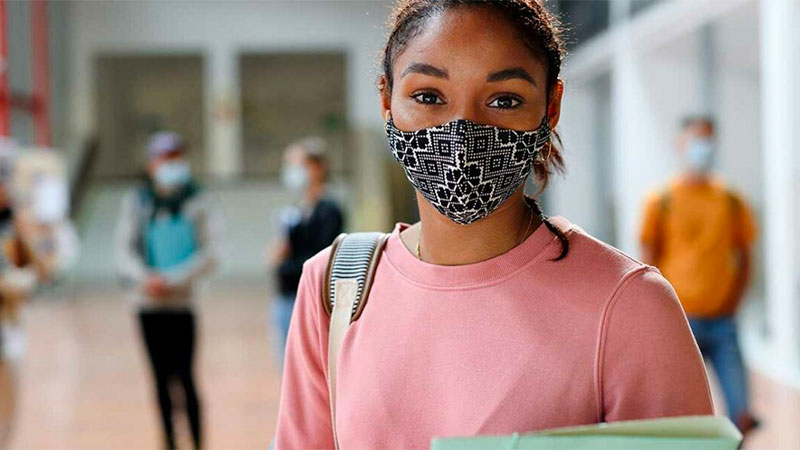 Black female student wearing a COVID mask, pink sweatshirt, carrying a backpack.