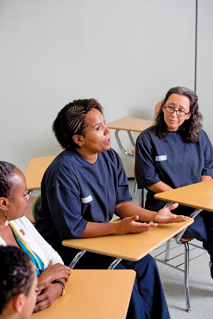 As Kimberly Fry (right) listens attentively, Penny Juan makes a point during a Prison Bridge Program class held in the Rhode Island women's unit.