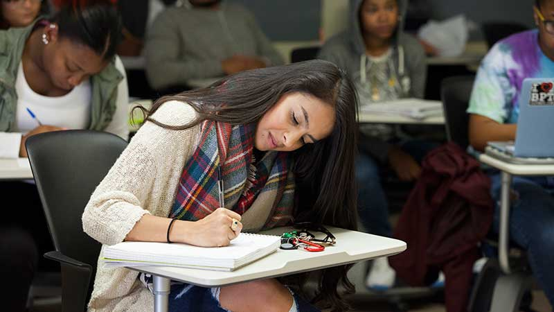 DACA student Laura Piñeros at desk in a full classroom writing in a notebook.