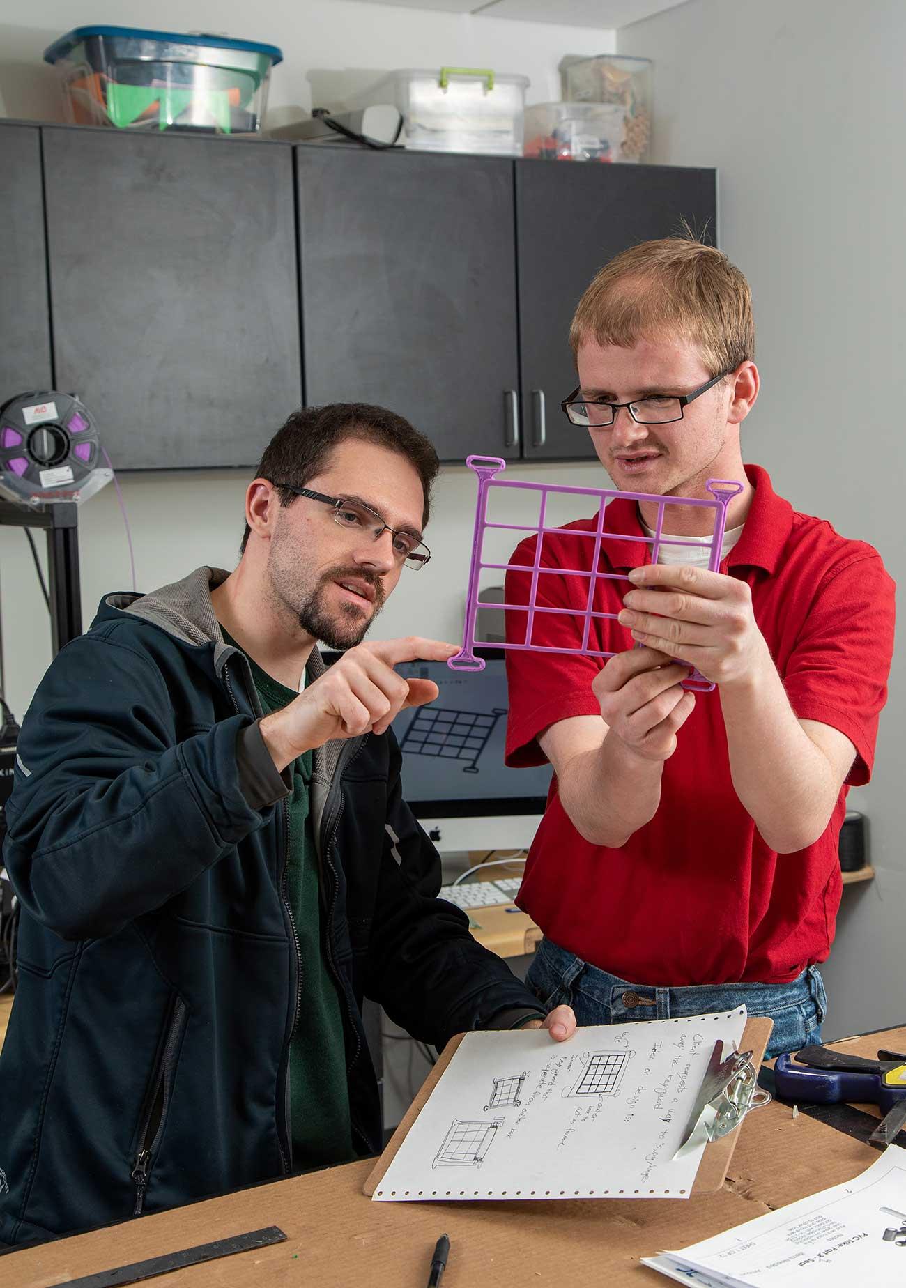 Student Trevor Larsen holds up a magenta 3d printed part for inspection.
