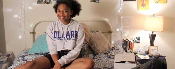 Dillard sophomore Khaelyn Jackson on bed with laptop and study materials.