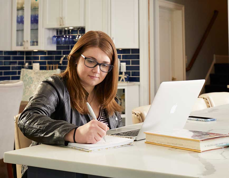 Kelsey Borror studying in her kitchen.