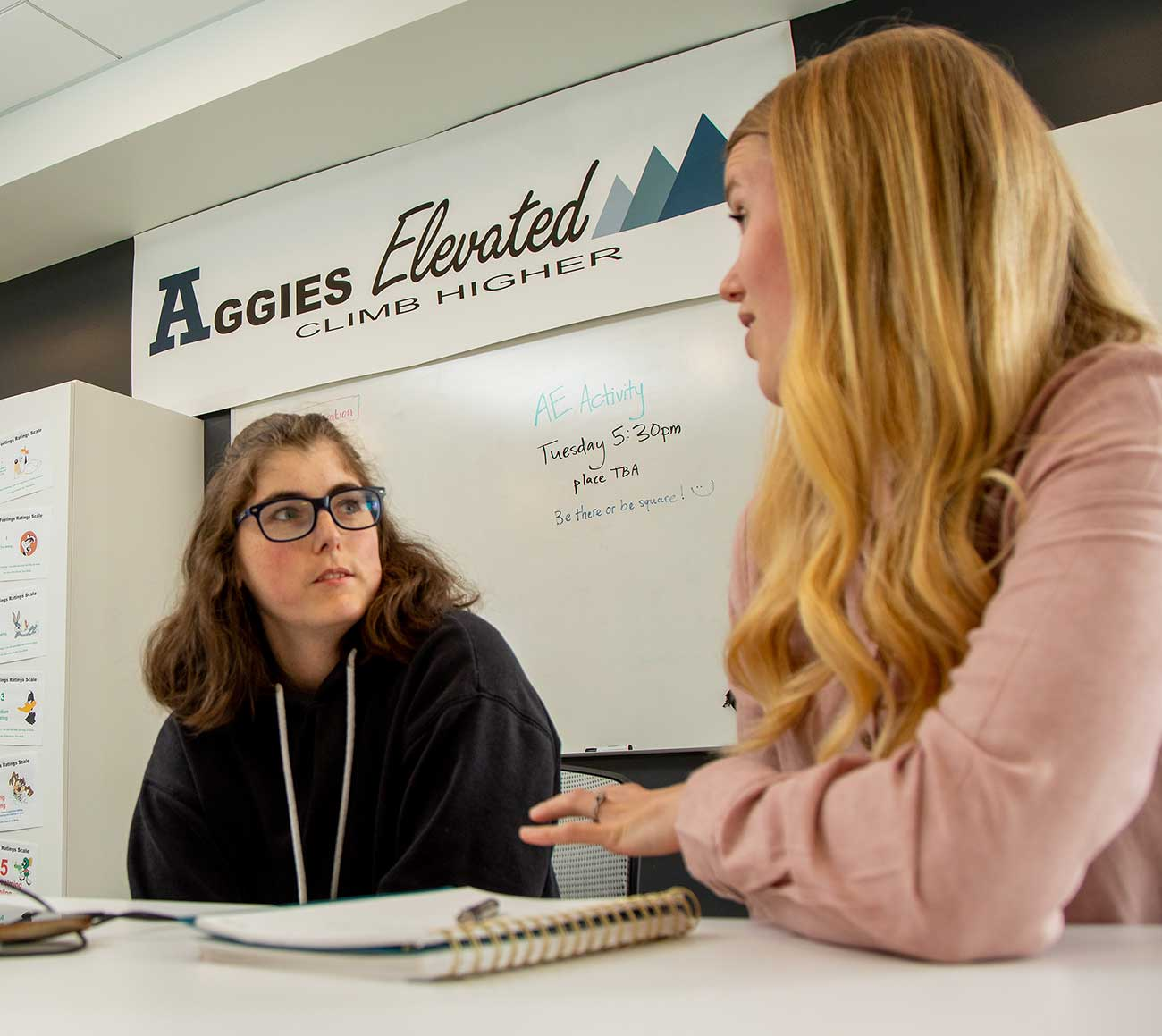 Student and mentor conversing. A spiral bound notebook is on the desk. An Aggies Elevated banner is visible in the background.