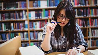 Stock photo: student in library, pencil in mouth