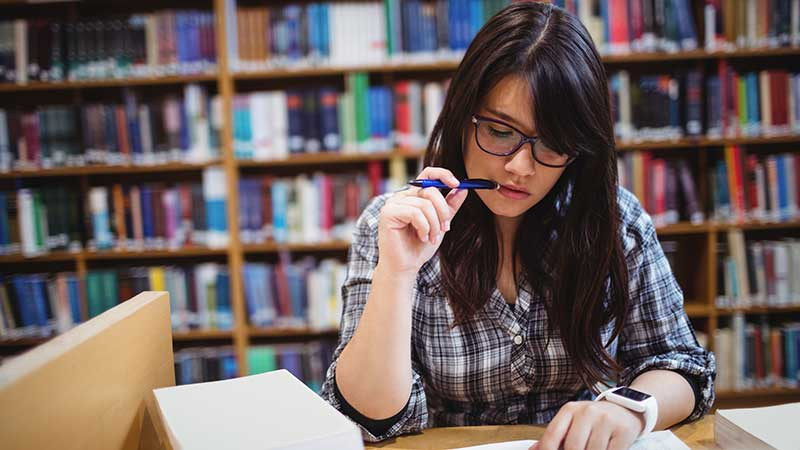 Stock photo: female student studying, pencil in mouth