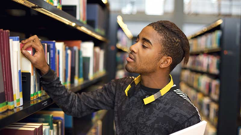 Black student exploring library stacks