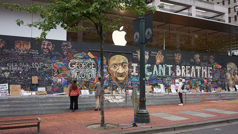 Portland, OR, USA - Jun 12, 2020: Passers-by stop and take a look at the boarded-up Apple Store in downtown Portland's Pioneer Place, which has become unofficial canvases for peaceful protest. Artists have also joined to promote peace over violence.