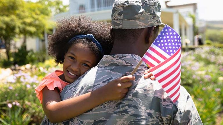 Black soldier holding daughter, stock photo