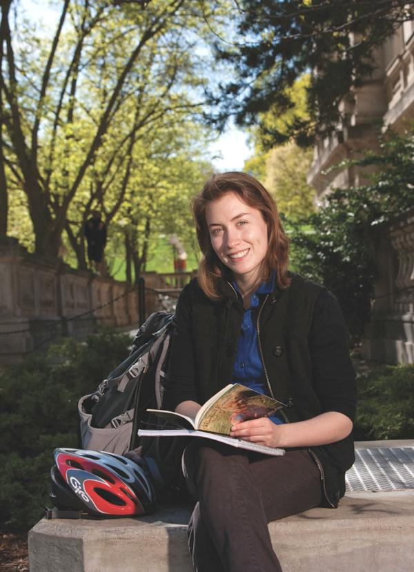 UW graduate Casmir Turnquist-Held is pictured seated on a concrete bench on campus. She has a book and notebook on her lap. Beside her is a large backpack and bike helmet.