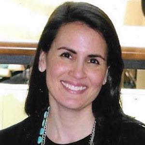 Outdoor picture of Christa Velasquez in front of white front door.