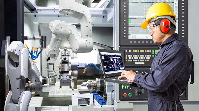 Stock photo of human working in tandem with a robot, or