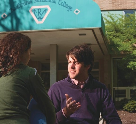 University of Wisconsin graduate John Fink talking with a colleague outside a Chadbourne Residential College building.