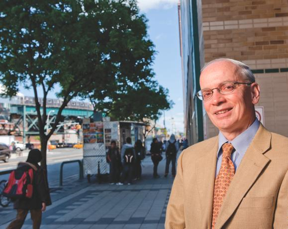 Paul Arcario, dean of academic affairs at LaGuardia Community College in a suitcoat and tie, photographed outside on a public street.