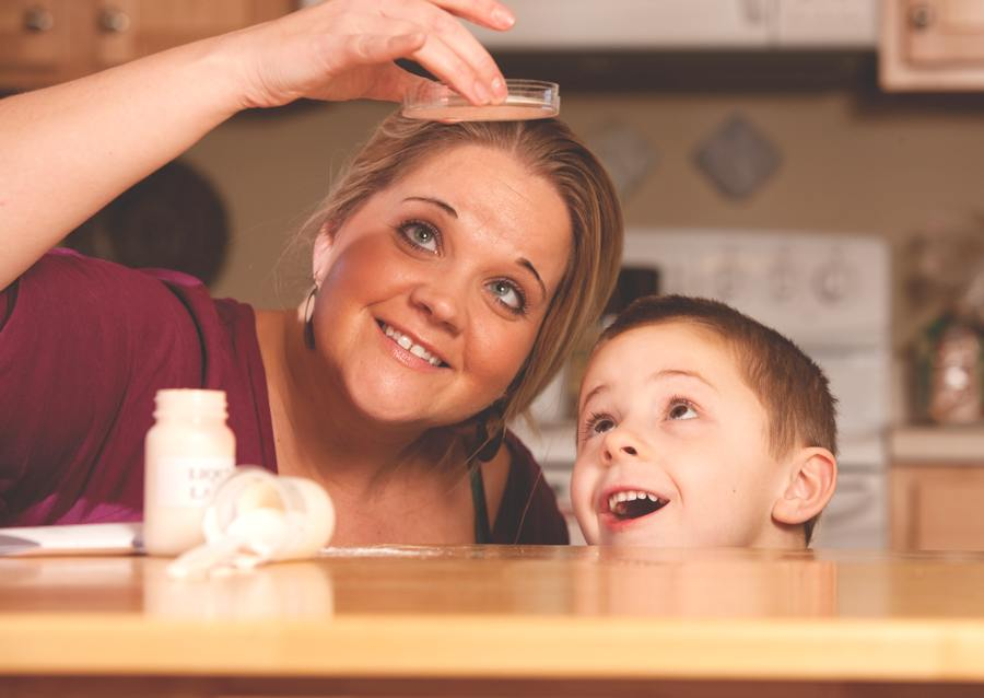 Shannon Adams of Martinsville, Ind. peers up into a petri dish in the light. He 5-year-old son looks up in clear fascination and delight.