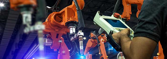 A dark factory floor with 3 large robotic manufacturing arms painted in bright orange. A man at the edge of the photo can be seen controlling the arms with a tablet device.