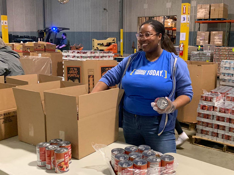 A worker in a food pantry warehouse with a big smile on her face packages canned food into cardboard boxes.