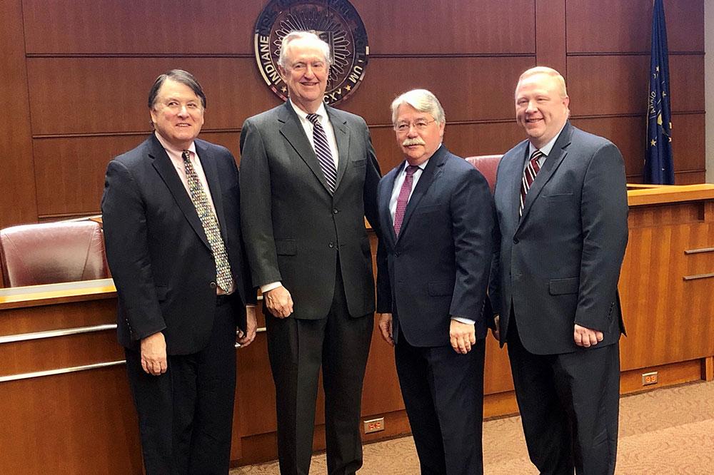 Four older gentlemen in suits.