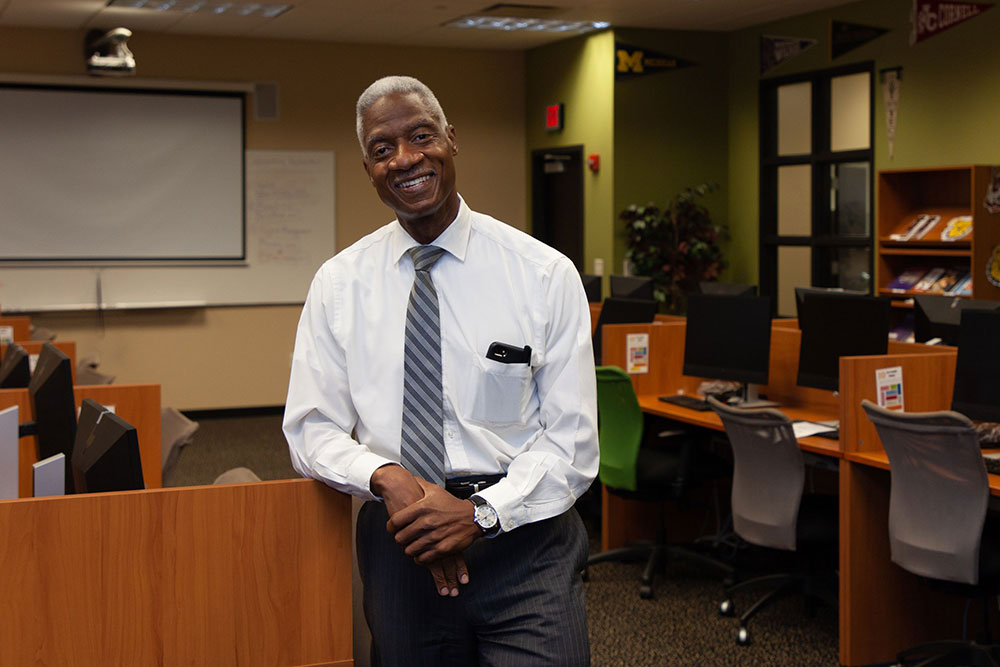 Dennis Bland, smiling in a long sleeved shirt and tie, leaning against a classroom desk.