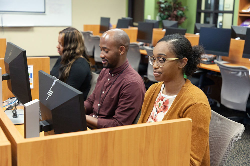 Three Black students at workstations at the CLD.