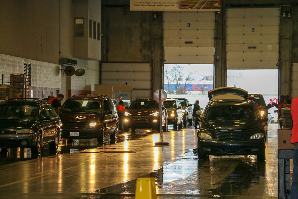 Two lines of cars wait for service in a high-ceilinged concrete hangar.