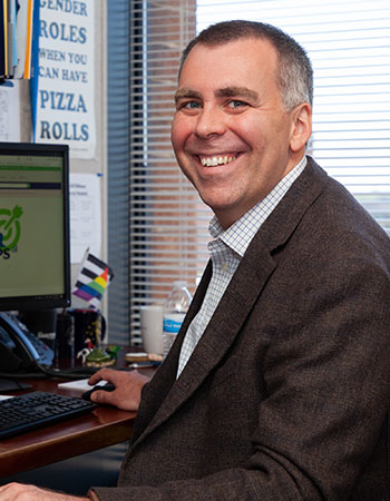 Mike Slocum of Indiana INTERNnet smiling at desk in an office high rise. A tablet, charter, and gay pride flag can be seen in his work environment.