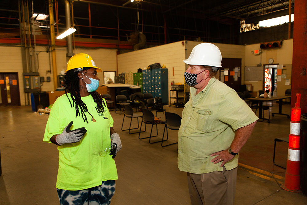 Workers in hard hats and COVID masks having a discussion in a work environment.