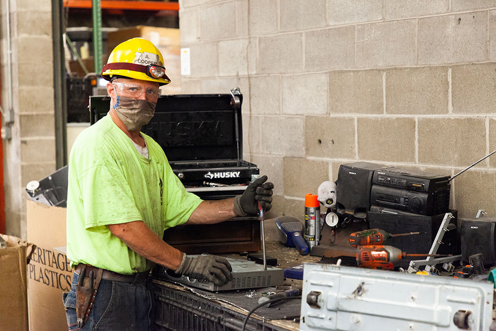 A man in a dirty fluorescent green shirt, plexi eye protection, and a yellow helmet with an attached work light is prying the plastic side off a video switcher with a long flat-head screwdriver.
