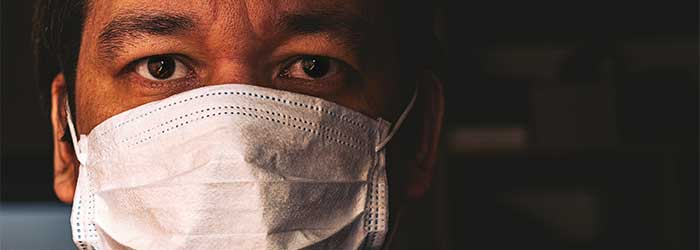 Close up of Black doctor's face mostly covered by a COVID mask.