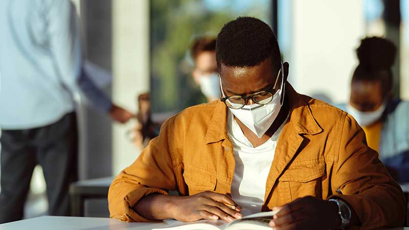 Black student reading and wearing COVID mask.