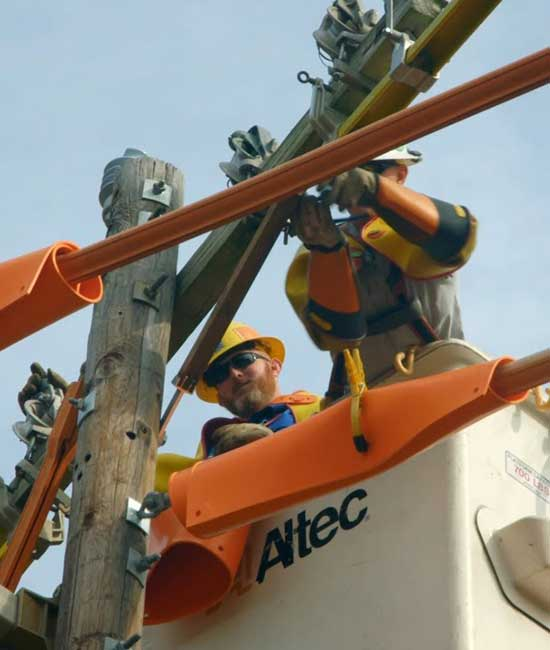 Two workers in a cherry picker working on line poles.