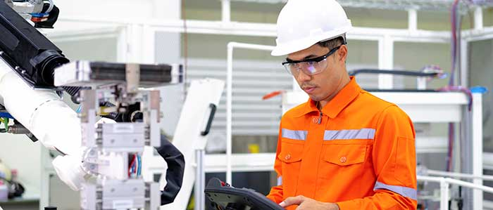 Worker in orange safety suit and helmet operating machinery