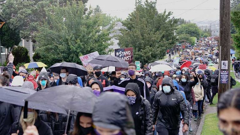 Silent protesters march in the rain through neighborhoods in Seattle calling attention to the Black Lives Matter Movement and Police Brutality.