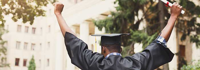 Black man at graduation holding his diploma victoriously high in the air.