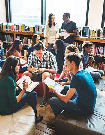 Students circled and studying in a library.