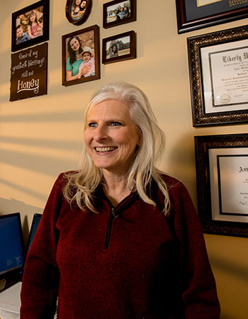 Lisa Villearreal smiling in front a wall on which her multiple diplomas hang.