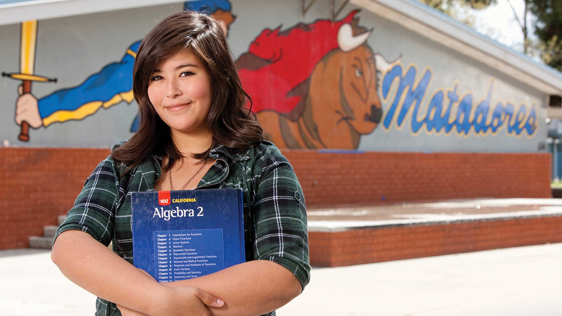 Latina student holding an algebra book standing in front of her school.