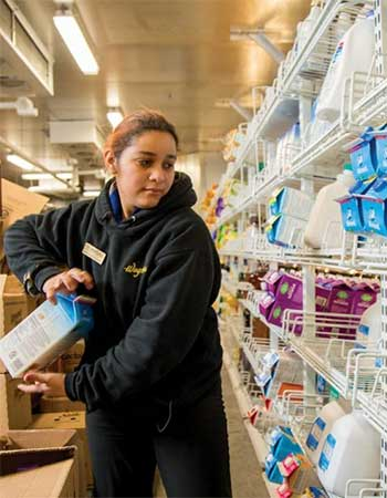 Female worker loading up almond milk in a grocery environment.