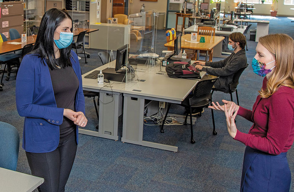 Inside the Academic Services center: two of its directors chat in COVID masks.