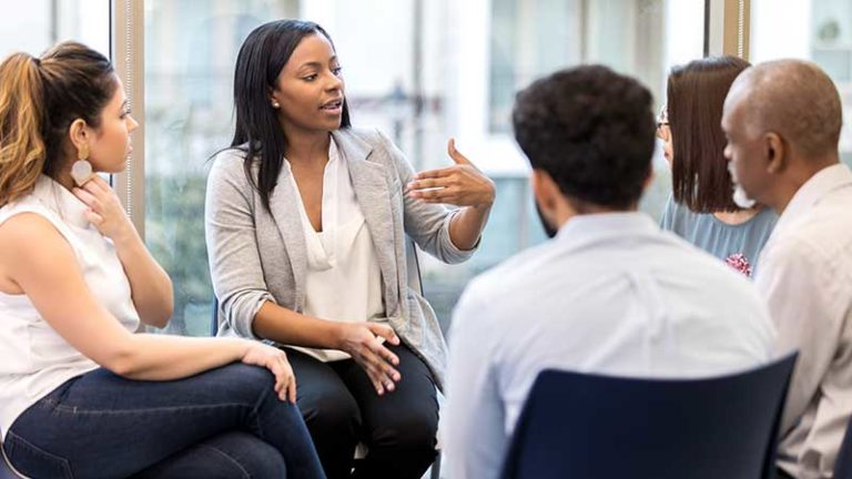 Black woman leading a roundtable discussion.