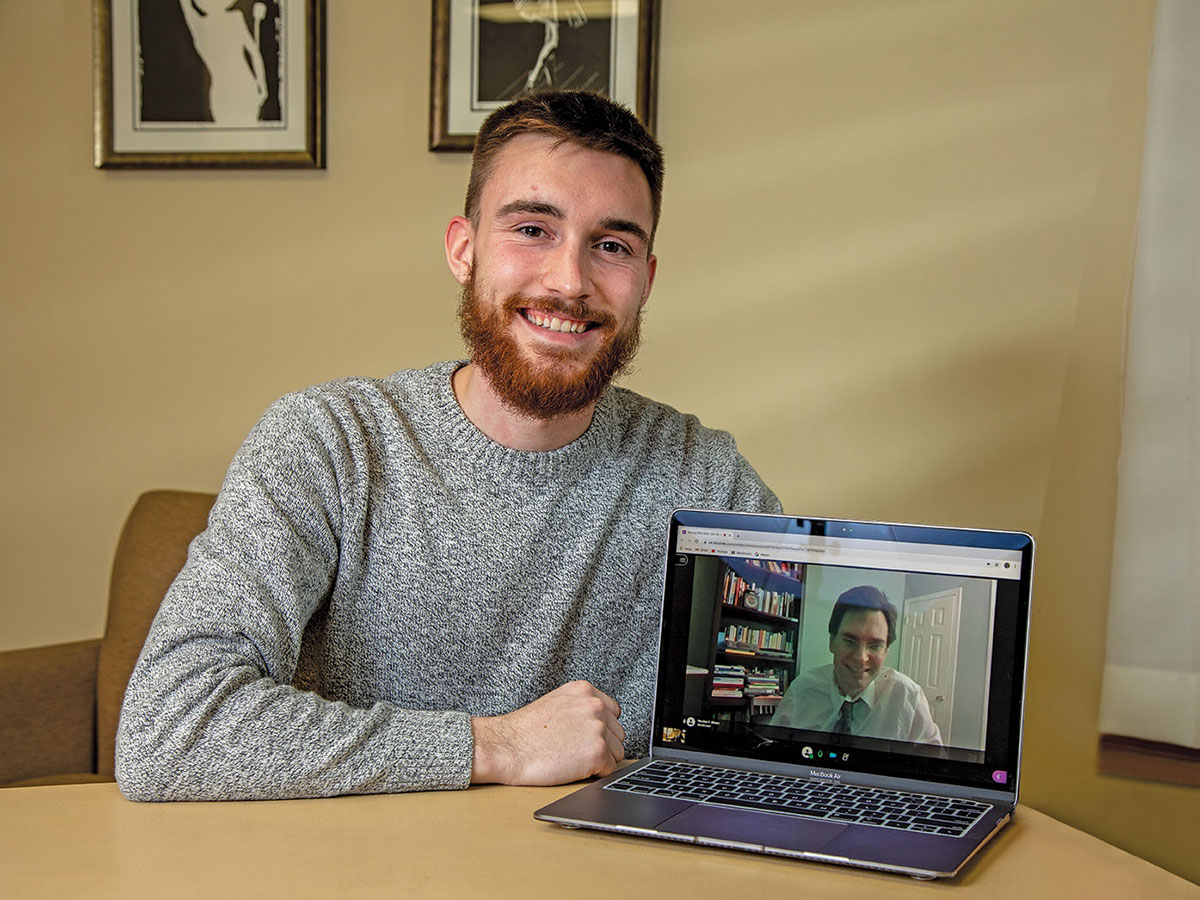 Brett Harrell smiling at a table. His laptop shows his a meeting attendee on screen.