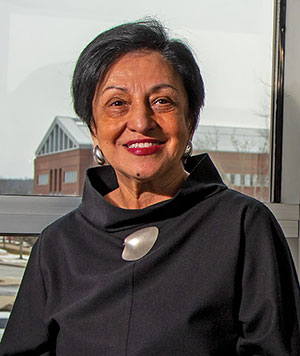 Elsa Núñez seated in front of a window, buildings in the background.