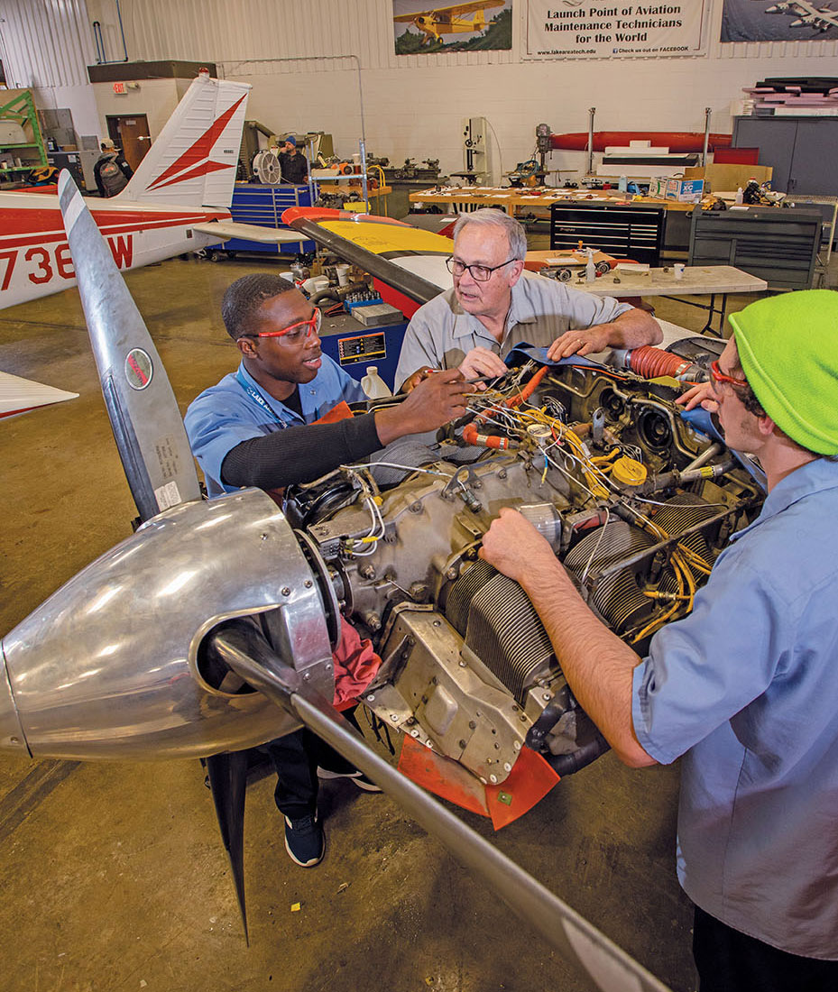Three men work together in an airplane hangar. All have their forearms resting on an open airplane propeller engine.
