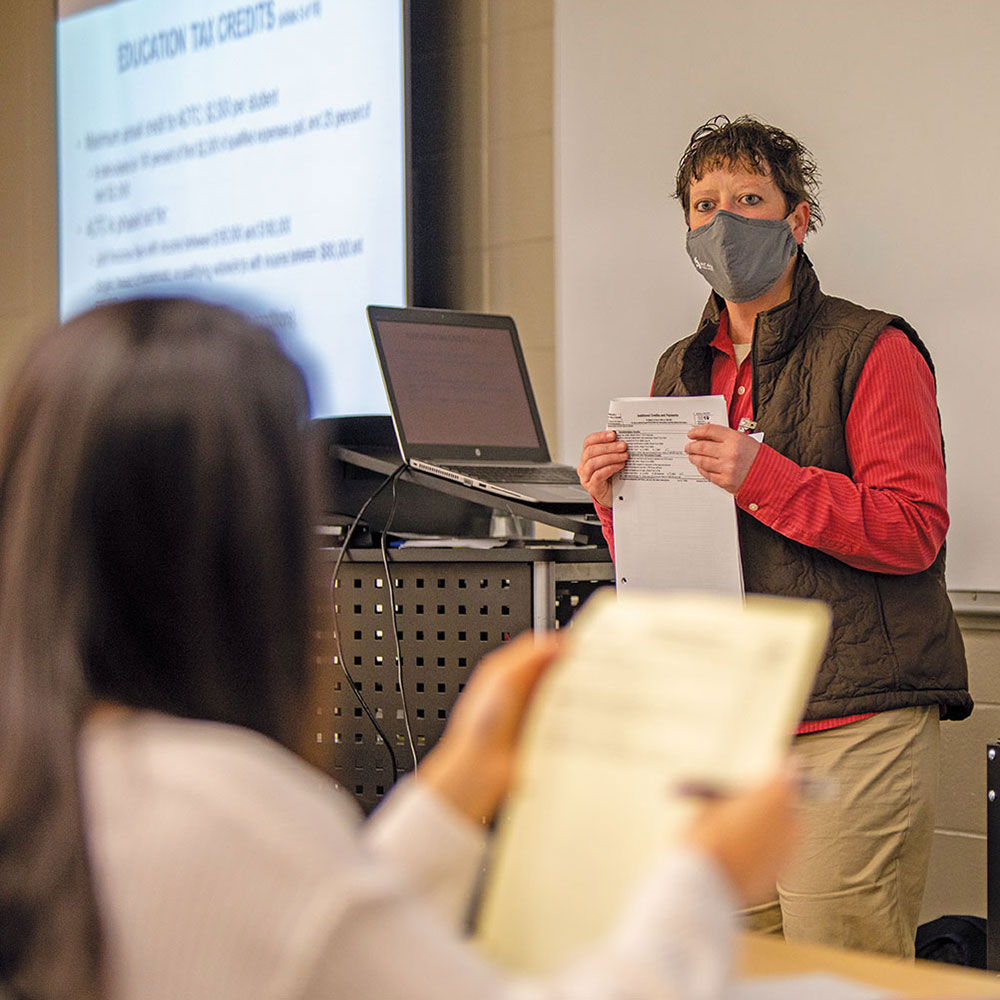 COVID-masked instructor in a vest leads a tax-preparation class. Her laptop is powerpoint is projected on a screen behind her.
