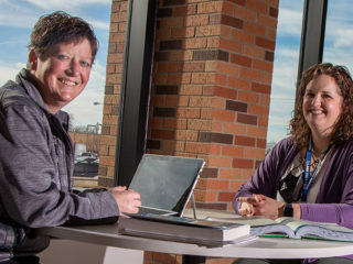 Instructors Lorna Hofer and Kerry Stager sit across from one another at a table in a common campus area.
