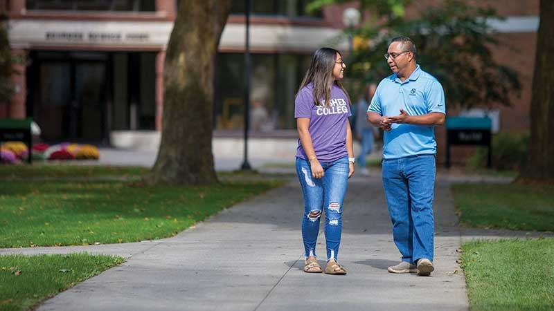 Manny Cortez walking with his 19-year-old daughter Kelly on the campus of Goshen College.