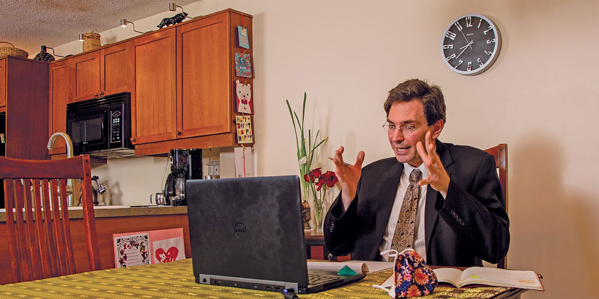 Assistant professor Nicolas Simon gesticulating at his laptop seated at his kitchen table.
