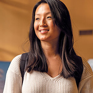 Asian woman in sweater, wearing backpack, smiling.