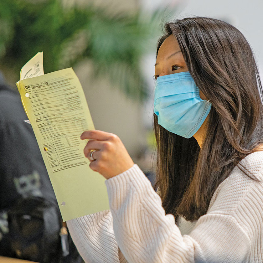 Same Asian woman from previous photo, here in a COVID mask, examines stapled sheets of a 1040 form.