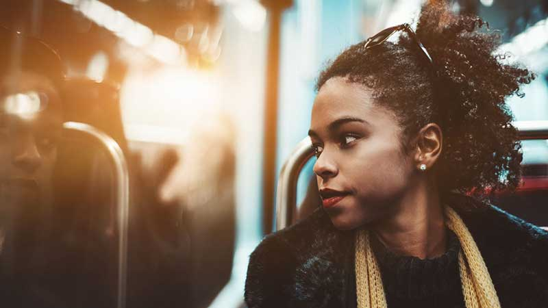 Black, female student on public transit.