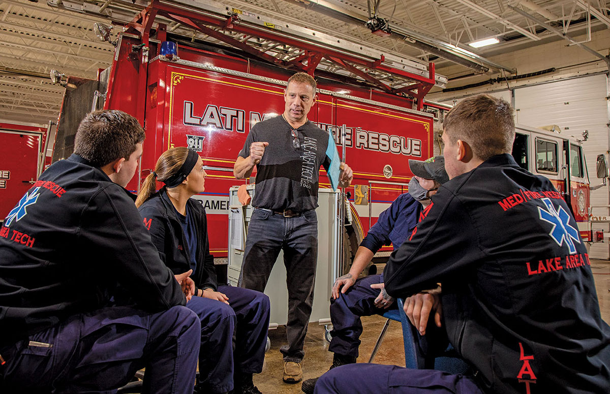 Seated students are instructed by a standing man. The students are wearing EMT uniforms. A fire truck in the background, the instruction takes place in an emergency medical garage.